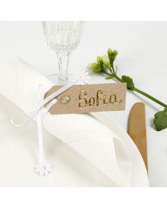 Una tarjeta de lugar de una etiqueta de manilla decorada con papel de aluminio, pedrería y cinta de raso