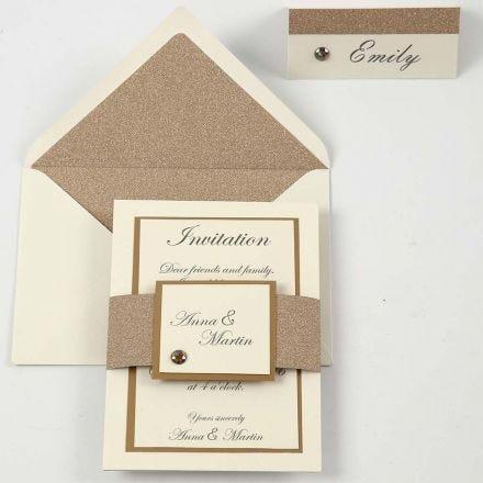 Una invitación y el porta nombres en cobre y blanco