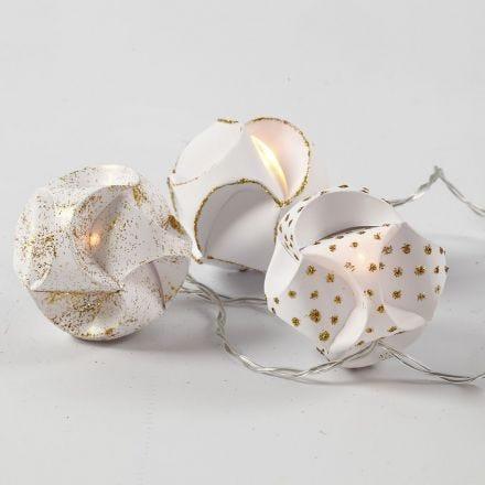 Luces LED en bolas de papel decoradas con cola de purpurina dorada