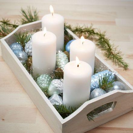 Una bandeja con cuatro velas y adornos de Navidad de vidrio y terracota pintados.