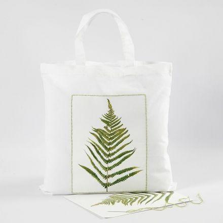 Una bolsa de compras con un diseño de hoja y un borde bordado