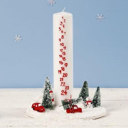 Una decoración con una vela de Adviento rodeada de un mundo de Navidad en miniatura