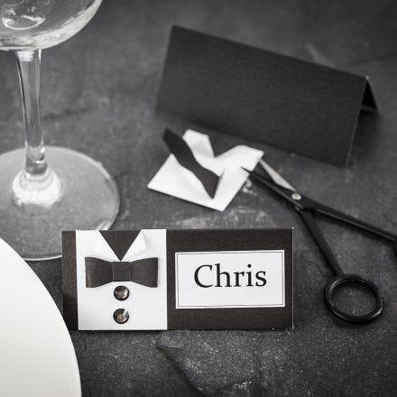 Una tarjeta de lugar para una fiesta de confirmación con una camisa y pajarito hechas de papel texturizado