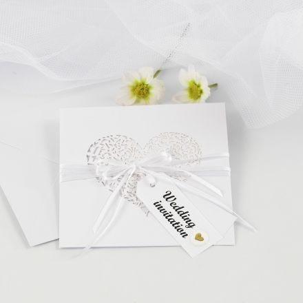 Una invitación de boda con cinta de raso y etiquetas manilla decoradas con pegatinas de relieve