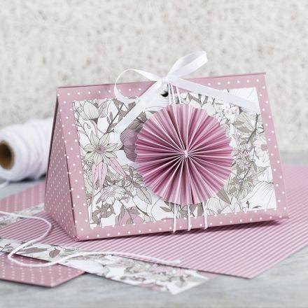 Una caja de regalo rosa con una roseta y papel de diseño.