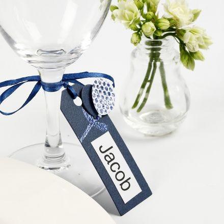 Una tarjeta de lugar con una etiqueta de manilla decorada con globos de cartulina y papel de aluminio