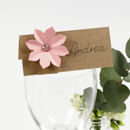 Una tarjeta de lugar decorada con una flor de cartulina con efecto 3D
