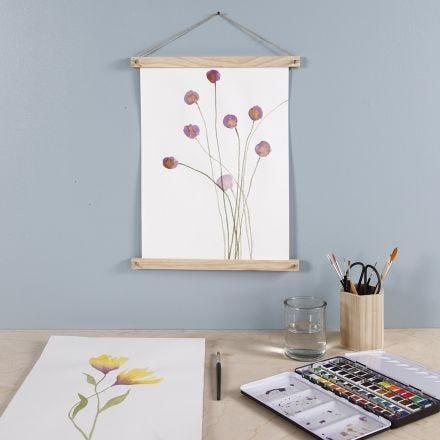 Una flor púrpura pintada con acuarelas y colgada con colgadores para póster.
