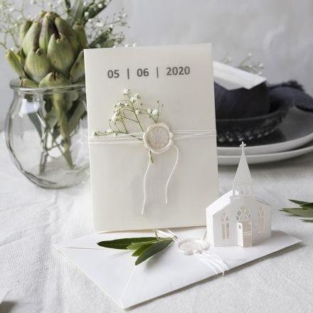Una invitación en tonos blanquecinos con una iglesia troquelada y papel vitela.