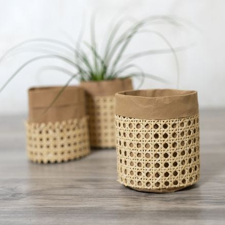 A storage bag from faux leather paper decorated with rattan