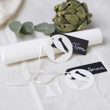 A wedding place card with a dress and a tie