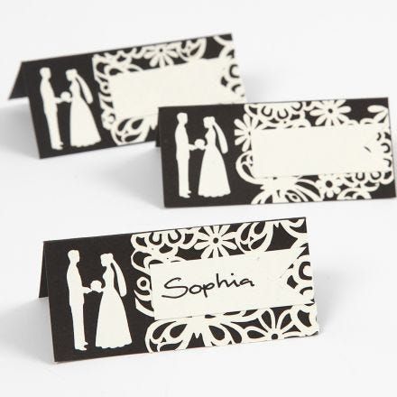A place card with a punched-out wedding design and laced card