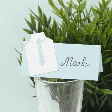Una tarjeta de lugar para fiesta de confirmación con una camisa hecha de cartulina y una corbata de papel.