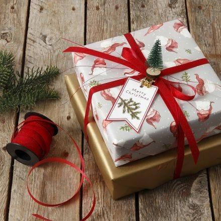 Envoltura de regalo de Navidad decorada con un mini árbol de Navidad en una clavija