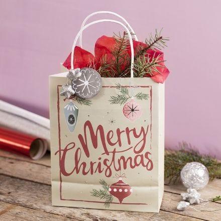 Una bolsa de regalo con un diseño navideño con una estrella, espumillón y papel china