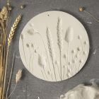 A plate from self-hardening clay with imprints of dried flowers
