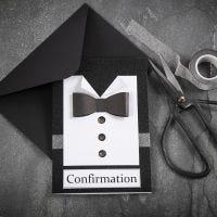 Una invitación en blanco y negro con una camisa y una pajarita hecha de papel texturizado y botones de piedras preciosas de imitación