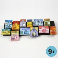 Lienzos con casas adosadas como un collage en una franja de madera