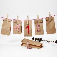 Un calendario hecho de bolsas de papel con números de washi tape