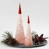 Un árbol de Navidad en forma de cono sobre una vela de te LED