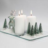 Una decoración de Navidad con velas, renos, árboles y nieve en un plato de vidrio