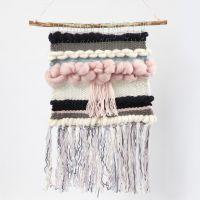Un tapiz tejido que cuelga de un palo de madera