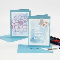 Una tarjeta de felicitación y una tarjeta de comensal con texto de goma de reserva pintado con acuarelas