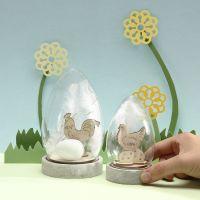 Una Campana Jar con figuras de Pascua de madera, huevos y plumas blancas