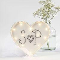Una caja de luz en forma de corazón decorada con pedrería y perlas