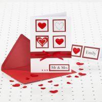Una invitación de boda roja y blanca con piedritas adhesivas.
