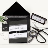 Una invitación de boda negra con bordes de washi tape