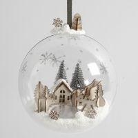Un mundo en miniatura de Foam Clay y figuras de madera en el interior de un adorno de Navidad