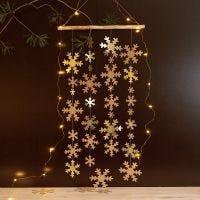 Una decoración colgante con papel de imitación de cuero, copos de nieve