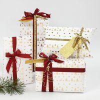 Envoltorio de regalo de Navidad blanco y dorado decorado con formas de alambre y cinta