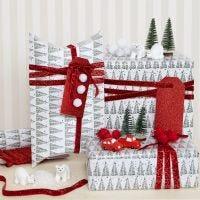 Papel de regalo navideño decorado con pompones y figuras en miniatura
