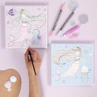 Un lienzo con un diseño de sirena decorado con rotuladores y pegamento glitter