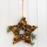 Una estrella de metal para una decoración de puerta decorada con conos, Lametta, etc.