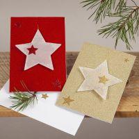 Tarjetas de Navidad brillantes con estrellas de vellum colgantes.