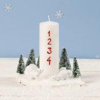 Una decoración de Navidad con una vela, miniatura de osos polares y árboles de Navidad