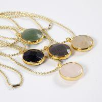 Un collar de cadena de abalorios y un colgante de joyería con una piedra