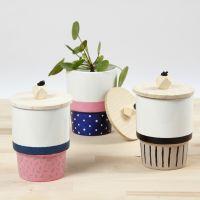 Una taza decorada con pintura de porcelana y una tapa con una cuenta de madera