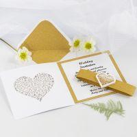 Una invitación de boda con papel de diseño dorado y una pegatina shaker en forma de corazón.