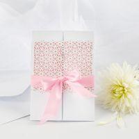 Una invitación de boda decorada con tarjeta de encaje y cinta de raso