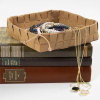 Una cesta tejida con tiras de tejido de imitación al cuero y asegurada con un cordón de cuero