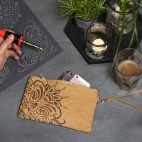 Una cartera de mano de papel imitación cuero con un diseño étnico usando una herramienta de pirograbado.