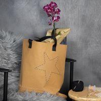 Una bolsa de papel imitación cuero con un borde bordado y una estrella.