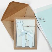 Una invitación para bautizo con una tarjeta de jirafa y cuentas de letras.