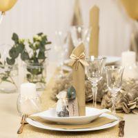 Decoraciones de mesa en dorado con flores de papel, globos, una servilleta doblada como una torre y tarjetas de lugar.