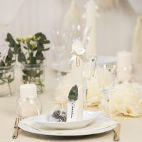 Decoración de mesa en blanco roto con flores de papel, , globos y tassels de papel de seda, una servilleta doblada como una torre