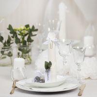 Decoraciones para mesa en blanco con flores de papel, globos, una servilleta enrollada como una torre y tarjetas de lugar.